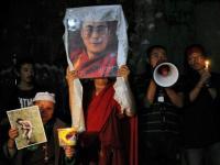 Tibetanos en el exilio con un retrato de su líder espiritual Dalai Lama, y una imagen de un joven tibetano que se inmoló (izq) el día antes, el 30 de septiembre en una vigilia en la localidad india de Dharamsala
